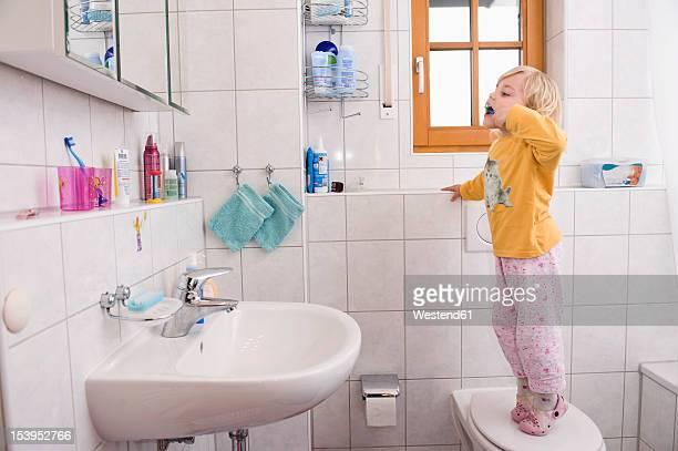 Girl standing on toilet, brushing teeth in bathroom