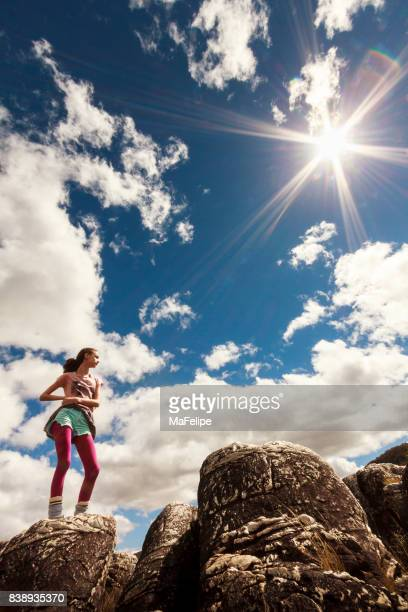 Girl standing on top of cliff