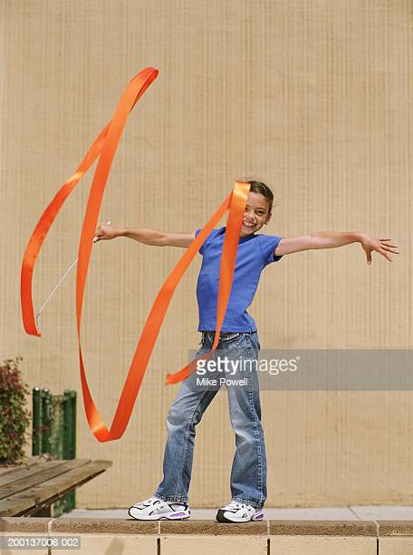 Girl (7-9) standing on wall, pretending to do rhythmic gymnastics
