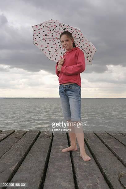 Girl (11-13), standing on wooden pier, holding umbrella, portrait