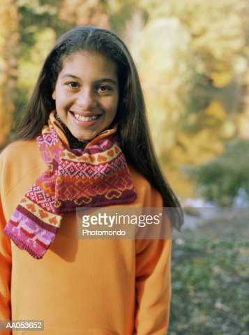 Girl (12-14) standing outdoors, smiling, portrait