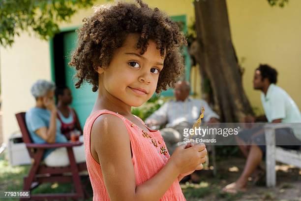 Menina em pé ao ar livre a sorrir com pessoas em segundo plano
