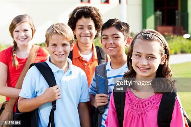 Niña de pie fuera de la escuela con un grupo de amigos