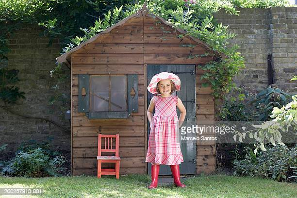 Girl (3-5) standing outside wendy house in garden, smiling, portrait