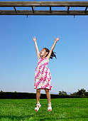 Girl (4-6) standing under monkey bars, arms outstretched