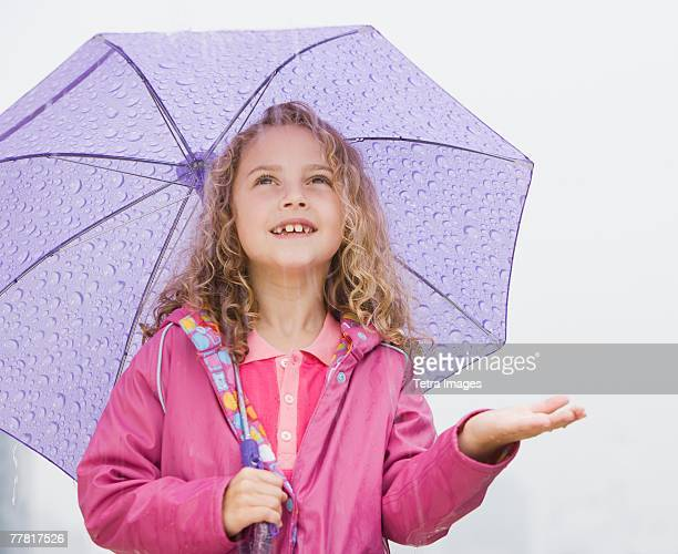 Girl standing under umbrella with hand out