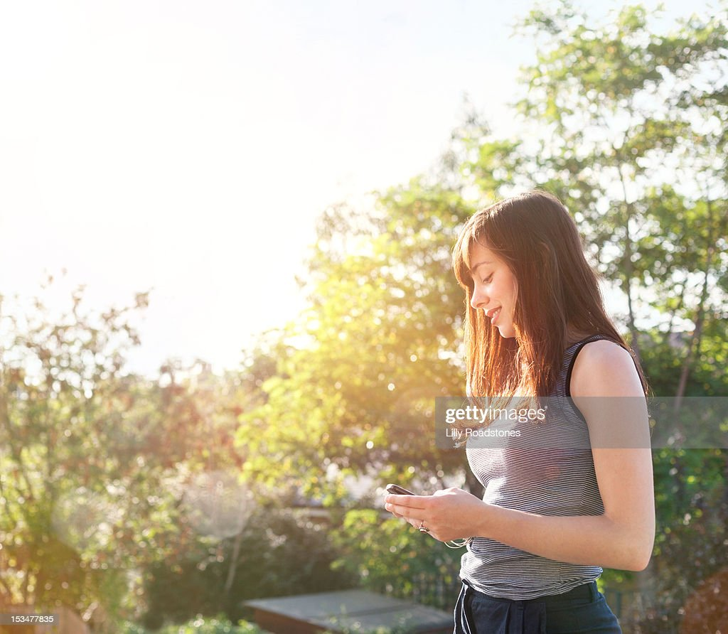 Girl standing using smartphone outdoors : Stock Photo