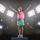 Girl (7-9) standing with arms raised in stadium (Digital Composite)