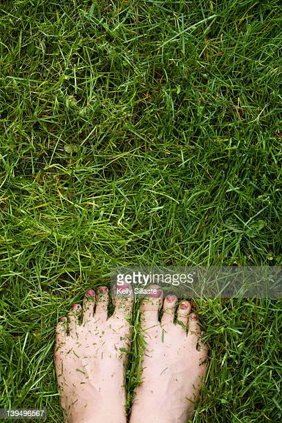 Girl standing with bare feet on fresh grass