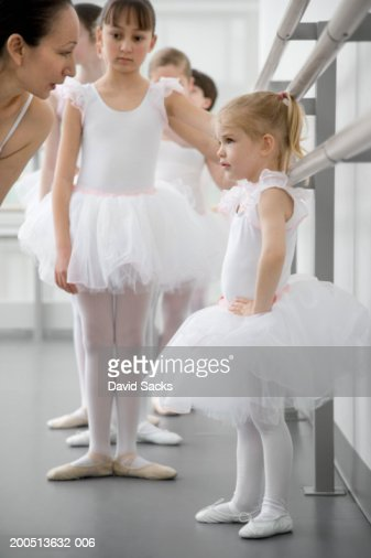 Girl (2-4) standing with hands on hips looking up at ballet teacher : Stock Photo