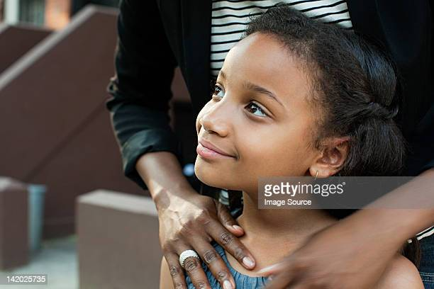 Girl standing with mother, looking away