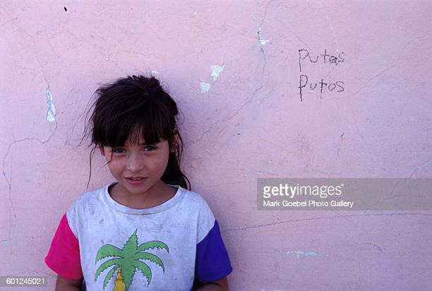A girl stands against a pink graffititagged wall Juarez Mexico late 1980s She is wearing a dirty tshirt with a design of a green plant