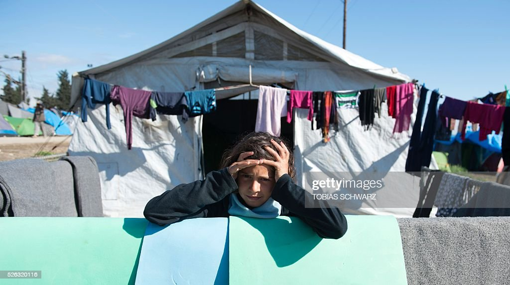 A girl stands among laundry lines hanging outside a tent at a makeshift camp for migrants and refugees near the village of Idomeni, not far from the Greek-Macedonian border, on April 30, 2016. Some 54,000 people, many of them fleeing the war in Syria, have been stranded on Greek territory since the closure of the migrant route through the Balkans in February. / AFP / TOBIAS