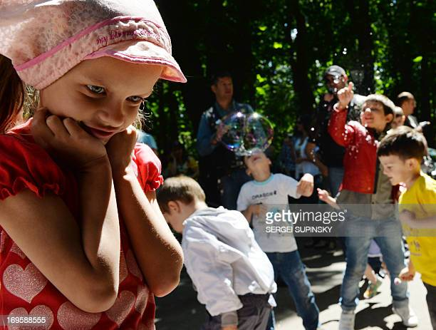 A girl stands as children play on May 28 2013 with soap bubbles during the Share Drive of Life charity event organized by the Kiev Chapter Ukraine...