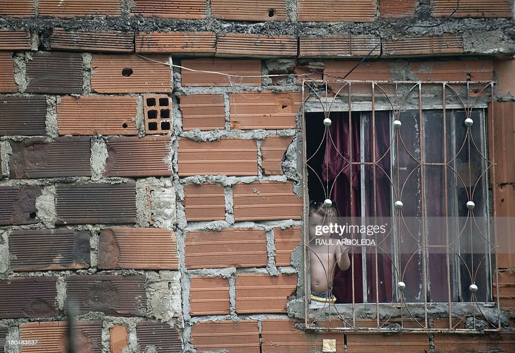 A girl stands at her home's window near to bullet holes on the wall at Comuna 8, one of the shantytowns with the highest rates of urban violence and displacement due to disputes between gangs for the control of territory, in Medellin, Antioquia department, Colombia on February 1, 2013. AFP PHOTO/Raul ARBOLEDA