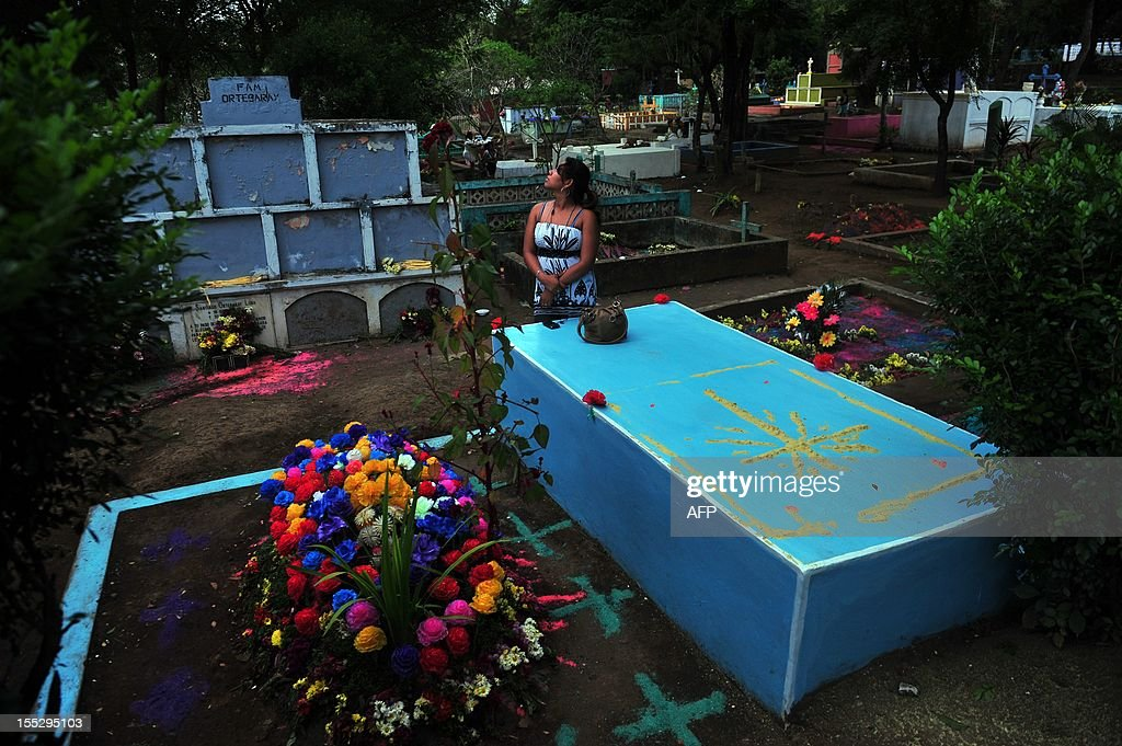 A girl stands by a relative's tomb at Monimbo cemetery in Masaya, 30 km from Managua on November 2, 2012, during All Souls Day. AFP PHOTO/Hector RETAMAL