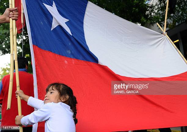 A girl stands next to a Chilean flag as a group gathers to show their support for the people of Aysen in southern Chile in front of the Chilean...