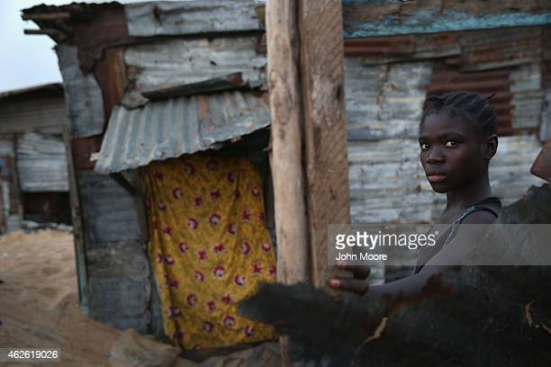 A girl stands outside her home in the West Point township on January 31 2015 in Monrovia Liberia Life has slowly begun to return to normal for many...