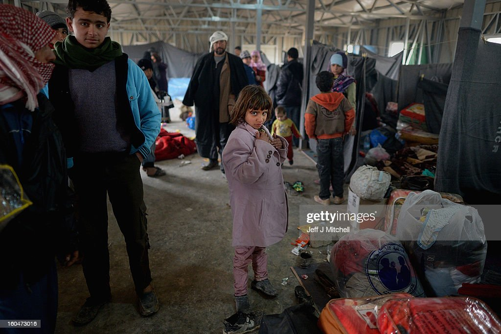 ZA'ATARI JORDAN FEBRUARY 01 A girl stands with bags and blankets as new Syrian refugees arrive at the International Organization for Migration at the...