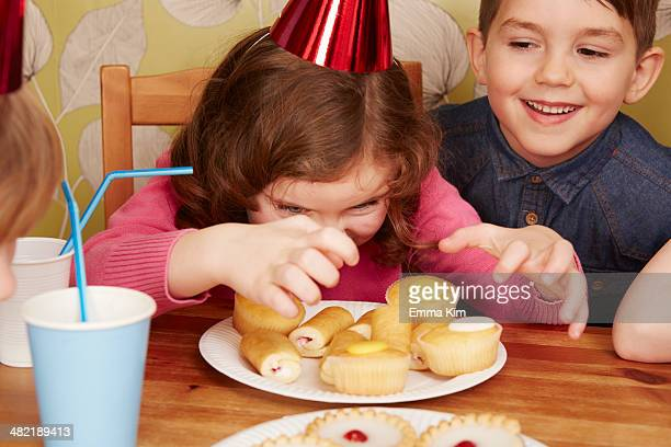 Girl staring at plate full of cakes