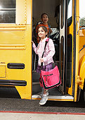 Girl (8-9) stepping off school bus, boy (8-9) standing behind