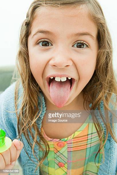 Girl sticking out tongue, holding lollipop