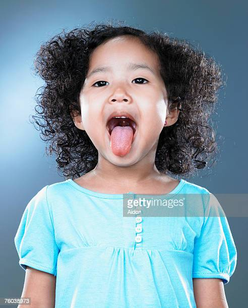 Girl (2-4) sticking out tongue