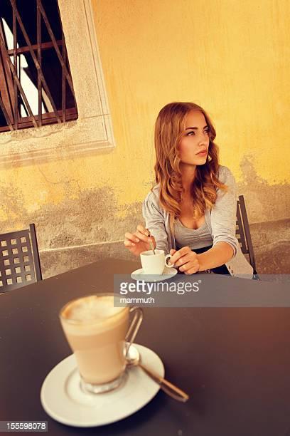 girl stirring coffee in an italian sidewalk cafe