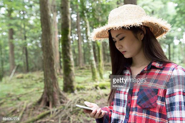 Girl straw hat use the smart phone in the forest.