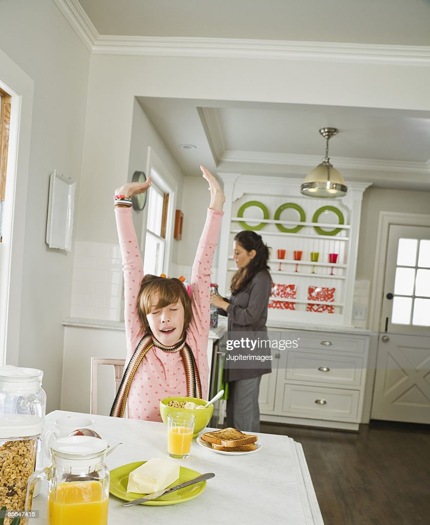 Girl stretching at breakfast table : Stock Photo