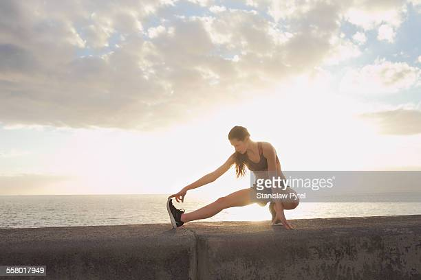 Girl stretching during workout near ocean, sunset