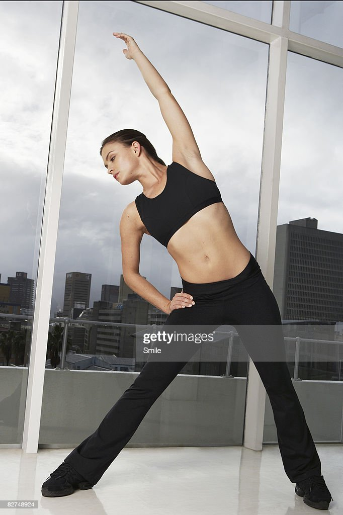 girl stretching in front of glass window : Stock Photo