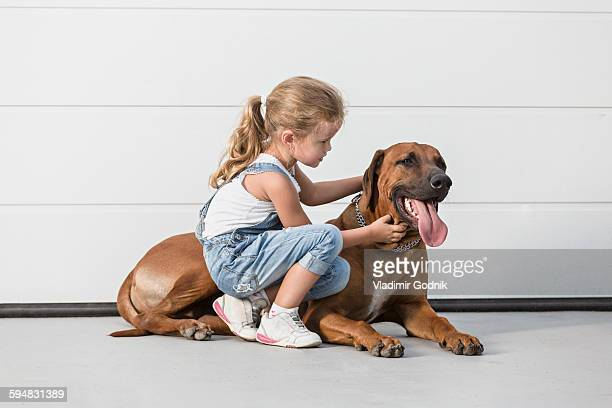 Girl stroking dog against white wall