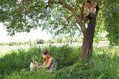 Girl (8-9) stroking dog, boy (8-9) climbing tree
