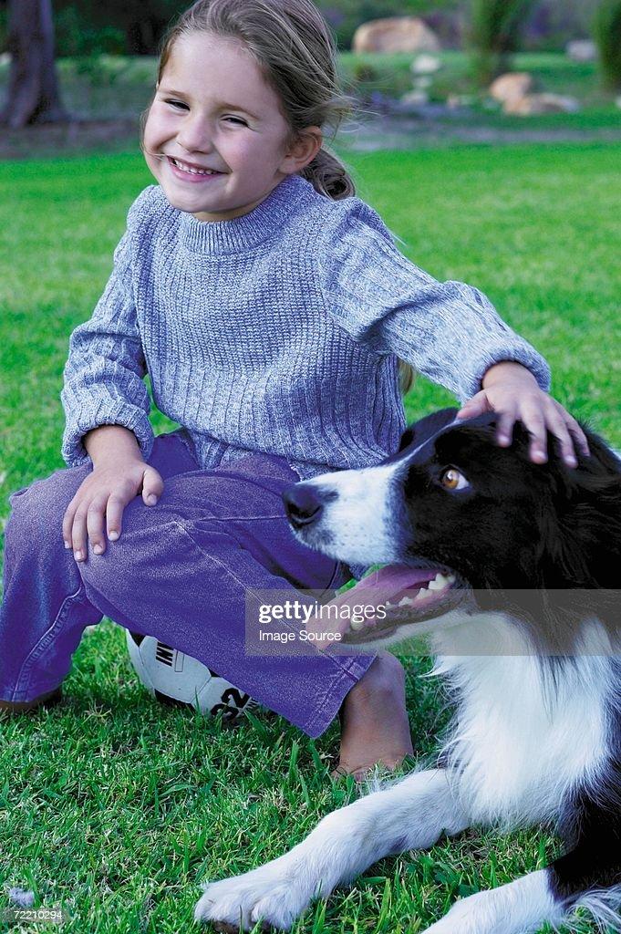 Girl stroking dog : Stock Photo