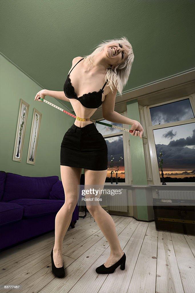 Girl struggling with her figure : Bildbanksbilder