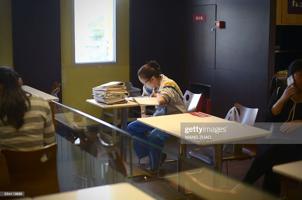 A girl studies at a restaurant in Beijing on May 26, 2016. / AFP / WANG