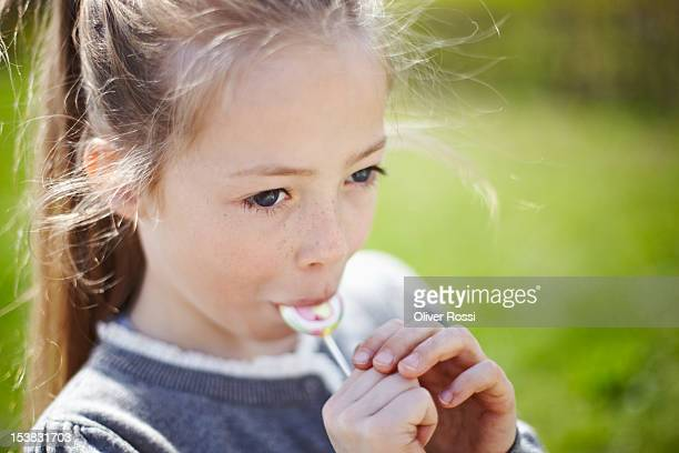Girl sucking a lollipop outdoors