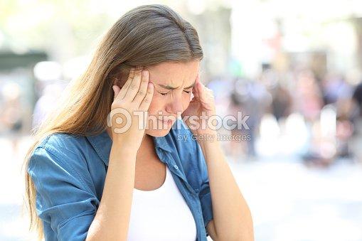 Girl suffering migraine in the street : Stock Photo