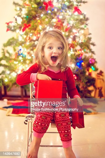 Girl surprised after opening Christmas gift : Stock Photo