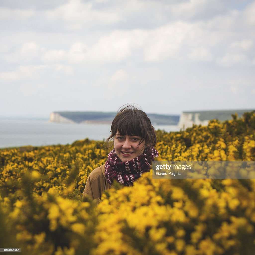 Girl surrounded by yellow flowers next to the sea : Stock Photo