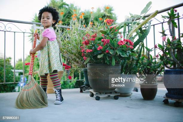 Girl sweeping patio with broom