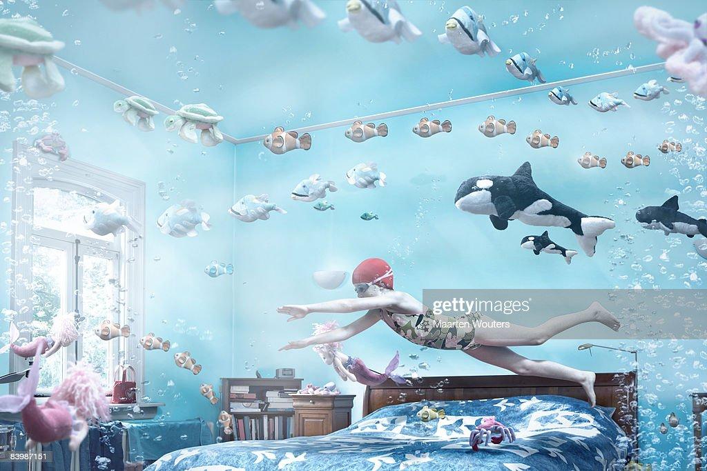 Girl swimming in her bedroom : Stock Photo
