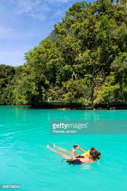 Girl swimming in the Milky Way Lagoon, Rock Islands, Palau