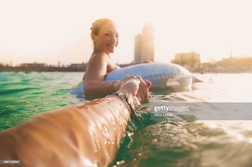 Girl swimming on inflatable ring pad on Mediterranean Sea with boyfriend taking his hand and taking picture from personal perspective with the skyline of the Barcelona city on sunset during summer time without stress and relaxing times. Follow me. : Stock Photo
