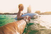 Girl swimming on inflatable ring pad on Mediterranean Sea with boyfriend taking his hand and taking picture from personal perspective with the skyline of the Barcelona city on sunset during summer time without stress and relaxing times. Follow me.