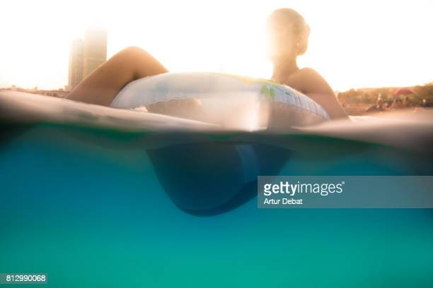 Girl swimming on inflatable ring pad on Mediterranean Sea with the skyline of the Barcelona city on sunset during summer time without stress and relaxing times.