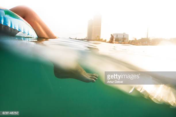 Girl swimming on inflatable ring pad with underwater view on Mediterranean Sea with the skyline of the Barcelona city on sunset during summer time without stress and relaxing times.