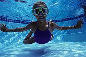Girl (8-9) swimming underwater, underwater view