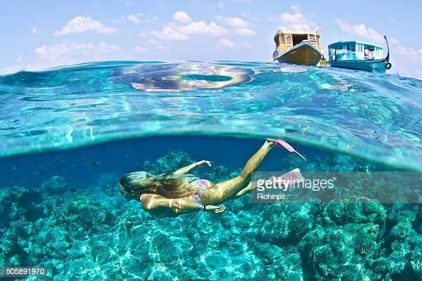 Girl swims beneath the sea with boats above